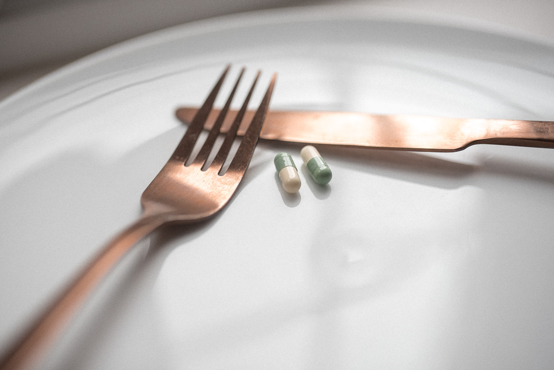 The dangers of laxative abuse in eating disorders - Pills on a an empty plate with a knife and fork